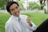 Businessman sitting in park, holding disposable cup - Asia Images Group
