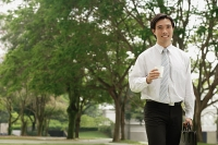 Businessman carrying briefcase and Styrofoam cup, outdoors - Asia Images Group