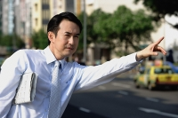 Businessman with newspaper under his arm, flagging a cab - Asia Images Group