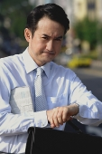 Businessman with newspaper under his arm, looking at watch, frowning - Asia Images Group