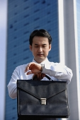Businessman looking at watch, frowning - Asia Images Group
