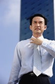 Businessman frowning, adjusting tie - Asia Images Group