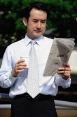 Businessman looking at newspaper, holding disposable cup - Asia Images Group