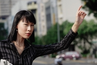 Businesswoman flagging a cab - Asia Images Group