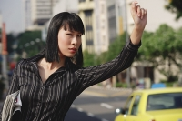 Businesswoman hailing a taxi - Asia Images Group