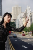 Businesswoman hailing a taxi with newspaper in hand - Asia Images Group