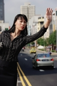 Businesswoman hailing a taxi, frowning - Asia Images Group