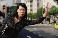 Businesswoman hailing a cab - Asia Images Group