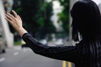 Businesswoman hailing a cab, rear view - Asia Images Group