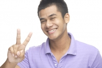 Man smiling at camera, making peace hand sign - Asia Images Group