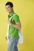 Man in green polo shirt, standing against yellow background, sunglasses on - Asia Images Group