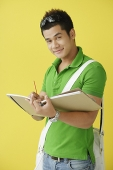 Man standing against yellow background, writing in notebook, looking at camera - Asia Images Group