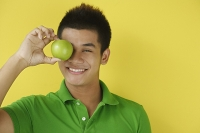 Man holding green apple over eyes, smiling at camera - Asia Images Group