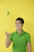 Man tossing green apple - Asia Images Group