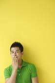 Man standing against yellow wall, covering mouth - Asia Images Group