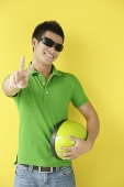 Man wearing sunglasses, making peace sign - Asia Images Group