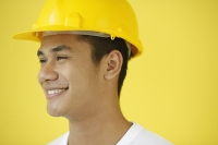 Man wearing hardhat, smiling, head shot - Asia Images Group