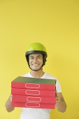 Pizza delivery person carrying a stack of pizza boxes - Asia Images Group