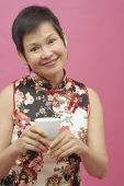 Mature woman cheongsam, holding Chinese tea cup - Asia Images Group