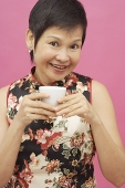 Mature woman holding Chinese tea cup, portrait - Asia Images Group