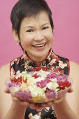 Mature woman holding bowl of flowers, smiling - Asia Images Group