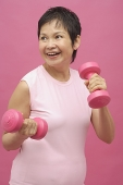 Mature woman using dumbbells - Asia Images Group