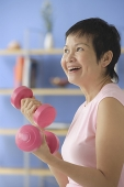 Woman at home, using dumbbells - Asia Images Group