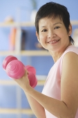 Mature woman holding dumbbells - Asia Images Group