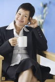 Business woman sitting on chair, holding mug - Asia Images Group