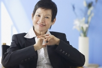 Business woman smiling at camera, hands clasped - Asia Images Group