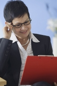 Business woman reading clipboard - Asia Images Group