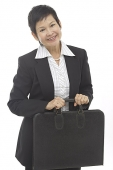 Mature businesswoman with briefcase, smiling at camera - Asia Images Group