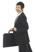 Businesswoman with briefcase, looking away, smiling - Asia Images Group