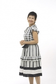 Mature woman against white background, smiling at camera - Asia Images Group