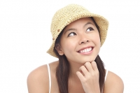 Young woman wearing hat, looking away, hand on chin - Asia Images Group