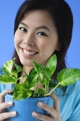 Young woman holding plant pot - Asia Images Group