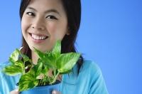 Young woman holding plant pot, portrait - Asia Images Group