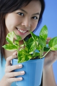 Young woman holding houseplant - Asia Images Group