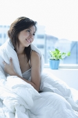 Young woman sitting on bed, wrapped in a blanket - Asia Images Group