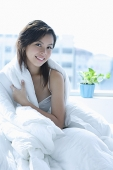 Young woman sitting on bed, wrapped in a blanket, smiling at camera - Asia Images Group