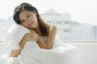 Young woman sitting on bed, embracing pillow - Asia Images Group