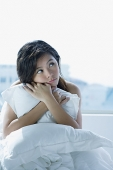 Young woman on bed, embracing pillow, looking away - Asia Images Group