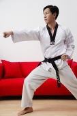 Man at home practicing martial arts - Asia Images Group
