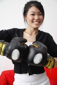 Young woman wearing boxing gloves, smiling at camera - Asia Images Group