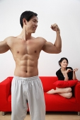 Couple at home, man in foreground showing off muscles, woman in background, sitting on sofa - Asia Images Group