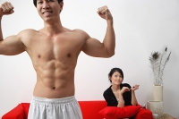 Couple at home, man in foreground flexing muscles, woman sitting on sofa - Asia Images Group