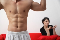 Woman sitting on sofa, filing her nails, man in foreground, flexing muscles - Asia Images Group