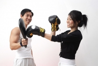 Young woman with boxing gloves, practicing with trainer - Asia Images Group