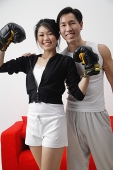 Couple smiling at camera, woman with boxing gloves - Asia Images Group