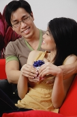 Couple sitting side by side, woman holding gift - Asia Images Group